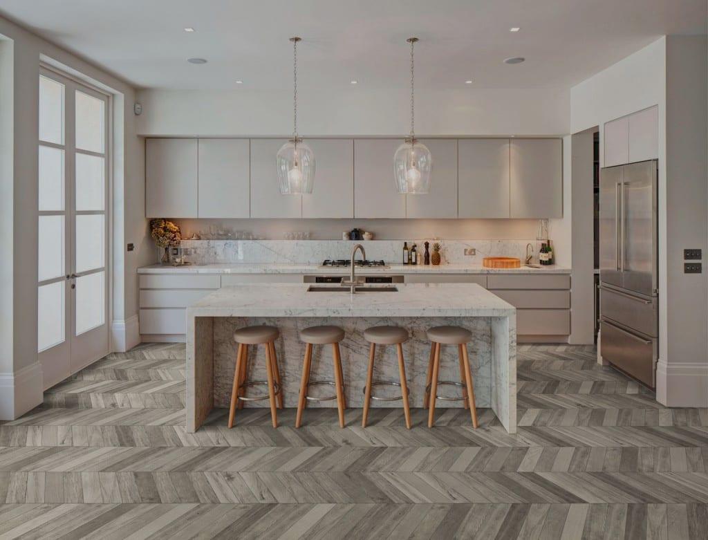 Oversiktsbilde av kjøkken med beige, jordnære fargetoner. Treverk fliser på gulv og marmor på vegg over kjøkkenbenken.