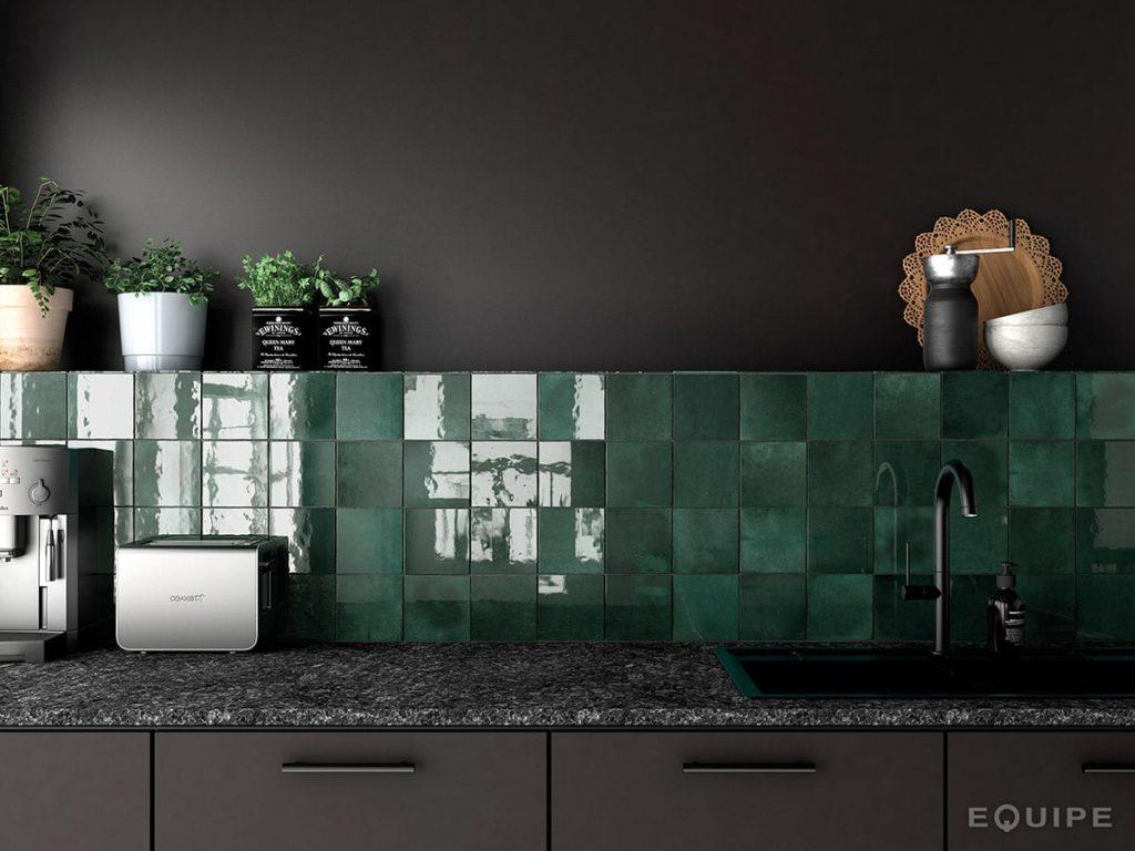 Detaljbilde av mosegrønne fliser på veggen over en kjøkkenbenk. Svartmalte skap og vegg rundt flisene.