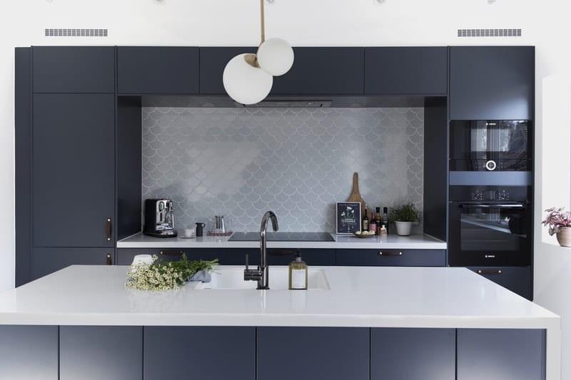 Oversiktsbilde av et kjøkken med gråe, vifteformede fliser. I forgrunnen er det en hvit benk med mørkegrå skap rundt.