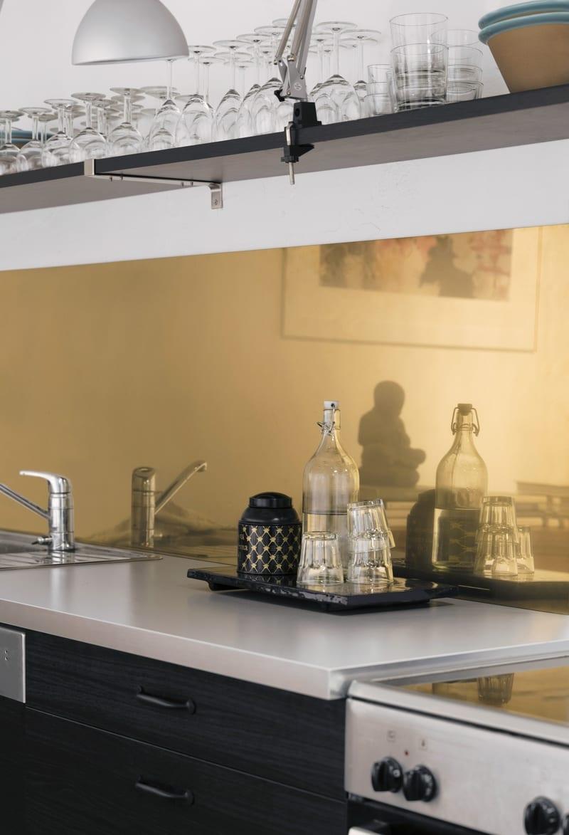 Nærbilde av veggen bak en kjøkkenbenk med gullflis.