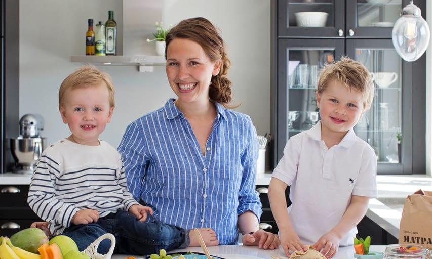 Mor og to barn på kjøkkenet, smilende mot kamera.