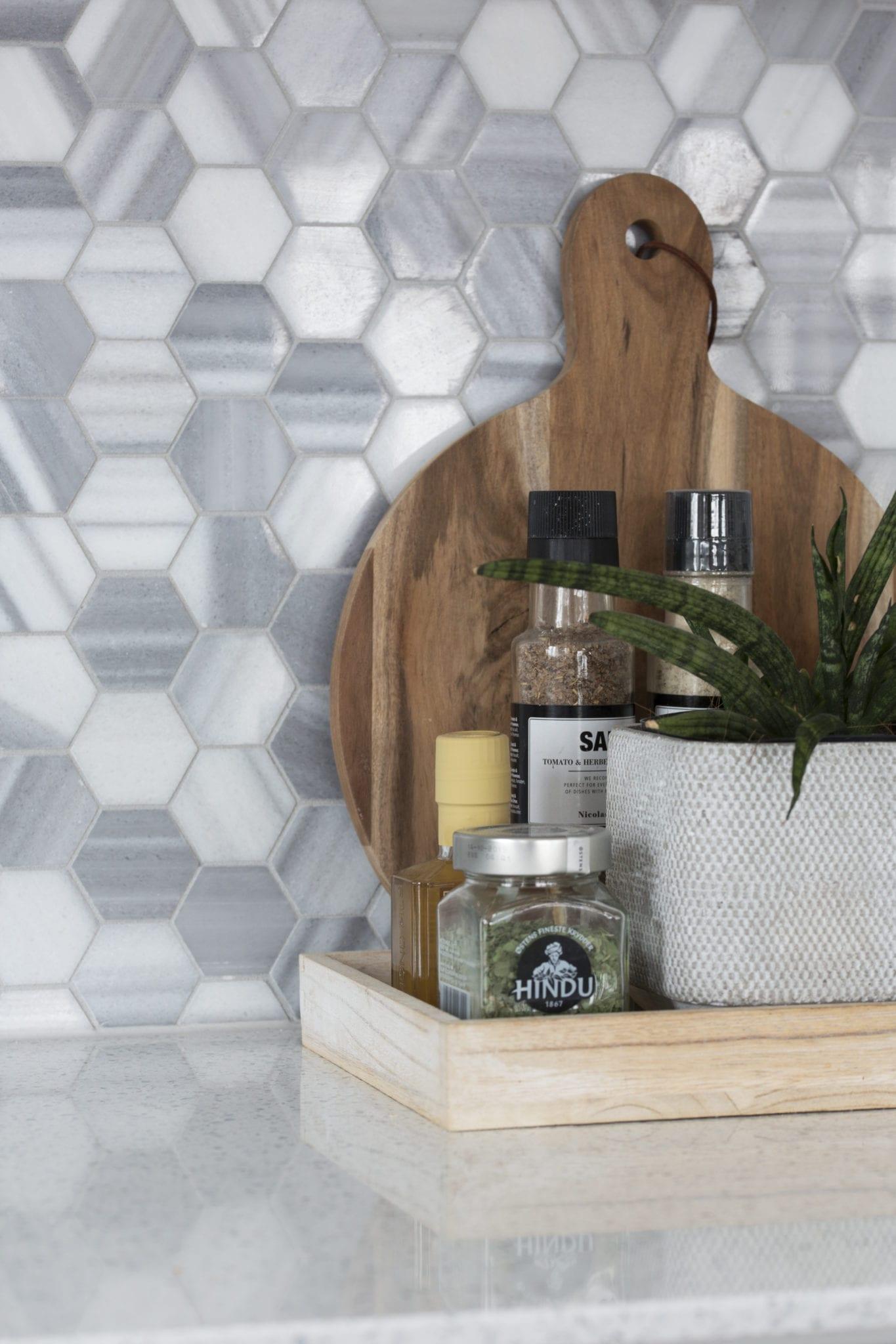 Detaljbilde av grå heksagonale fliser. I forgrunnen er det et skjærebrett med ulike kryddere foran.