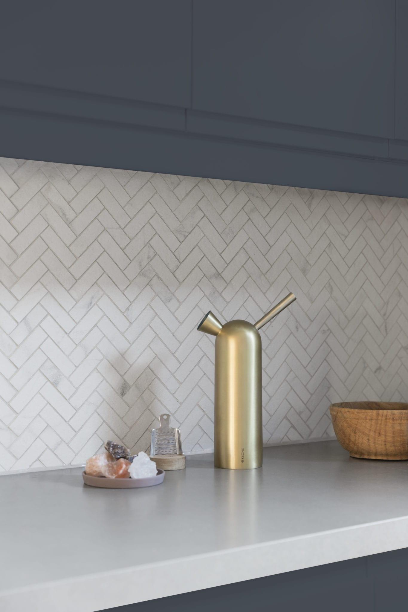 Nærbilde av hvite marmormosaikk fliser i fiskebein mønster.