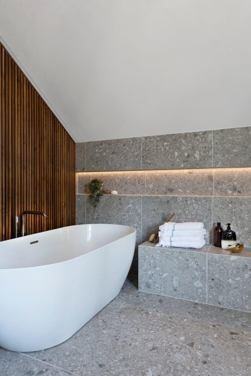 Bilde av hvitt badekar, steinfliser, hvitt tak og lun trevegg i valnøtt.
