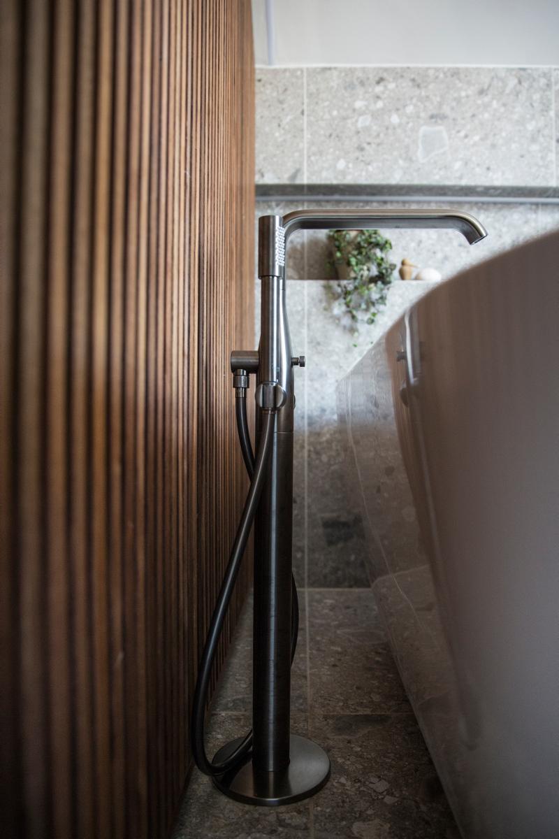 Bilde av badekarkran mellom lun valnøttvegg og hvitt badekar.